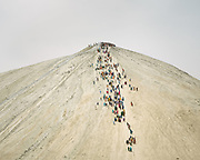"""Pilgrims climbing up the main volcano, some using a rope to help themselves up. The area around Chandragup (meaning """"Moon Well""""), a sacred site to Hindu of 3 mud volcanoes (mainland Asia's largest ones)."""