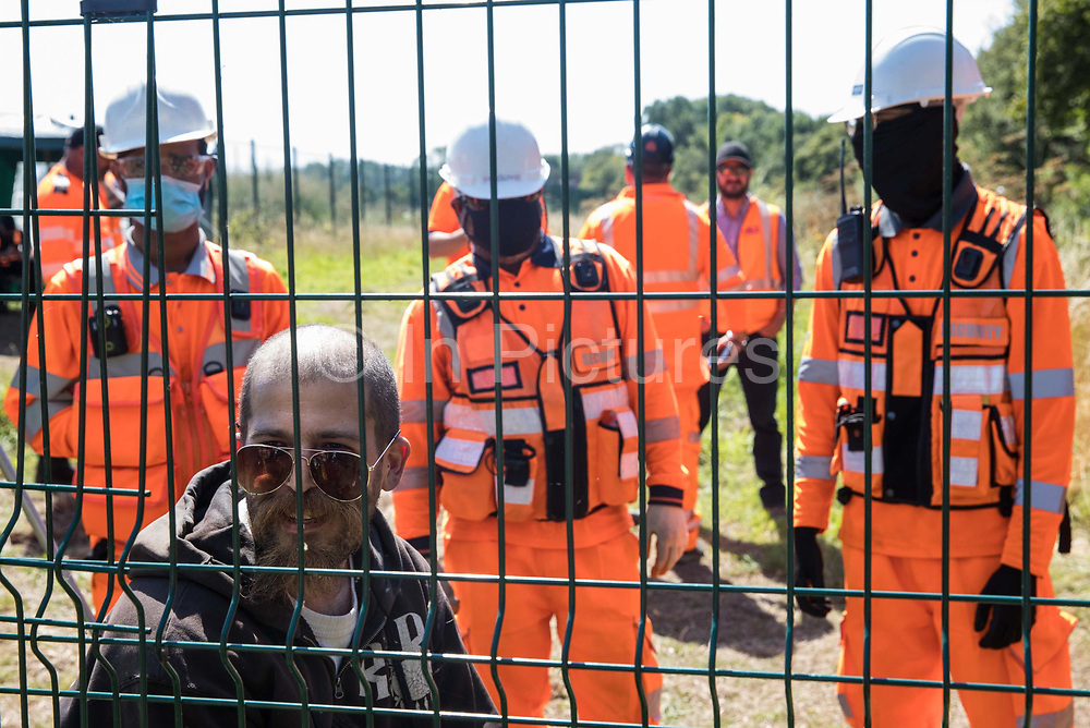 An environmental activist is monitored by HS2 security guards after climbing over a fence during the restaging of a historical 1602 visit by Queen Elizabeth I to Dews Farm on 31st July 2020 in Harefield, United Kingdom. The activists tried to retrace the steps of Queen Elizabeth I from St Mary's church to Dews Farm in order to pay their respects to Anne and Ron Ryall, 73 and 72, on the day of their eviction from Dews Farm by HS2 after having spent nine years and their life savings renovating their £1m dream home, but found their path blocked by HS2 fences and security guards.
