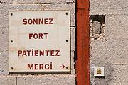 Sonnez Fort - Sing the bell hard. Patientez - wait. Merci - Thank you. Door bell. Domaine Ermitage du Pic St Loup, Chateau Ste Agnes. Pic St Loup. Languedoc. France. Europe.