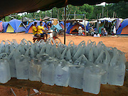 """Koh Lanta, Thailand--Bottled water supplied by the Thai government sits on a communal table waiting to be distributed to Hua Laem residents who lost their homes to the Tsunami on Koh Lanta Island, Thailand.  In the background are the tents provided by """"World Vision"""" which many of the villagers have been living in since the Tsunami hit December 26th.  Some residents stay in the tents, which are on the hill above their town, because they fear another Tsunami may come. 01/20/05 © Julia Cumes / The Image Works"""