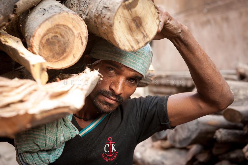 Portrait of a man carrying firewood near Manikarnika cremation ground, Varanasi, India. Photo ©robertvansluis.com