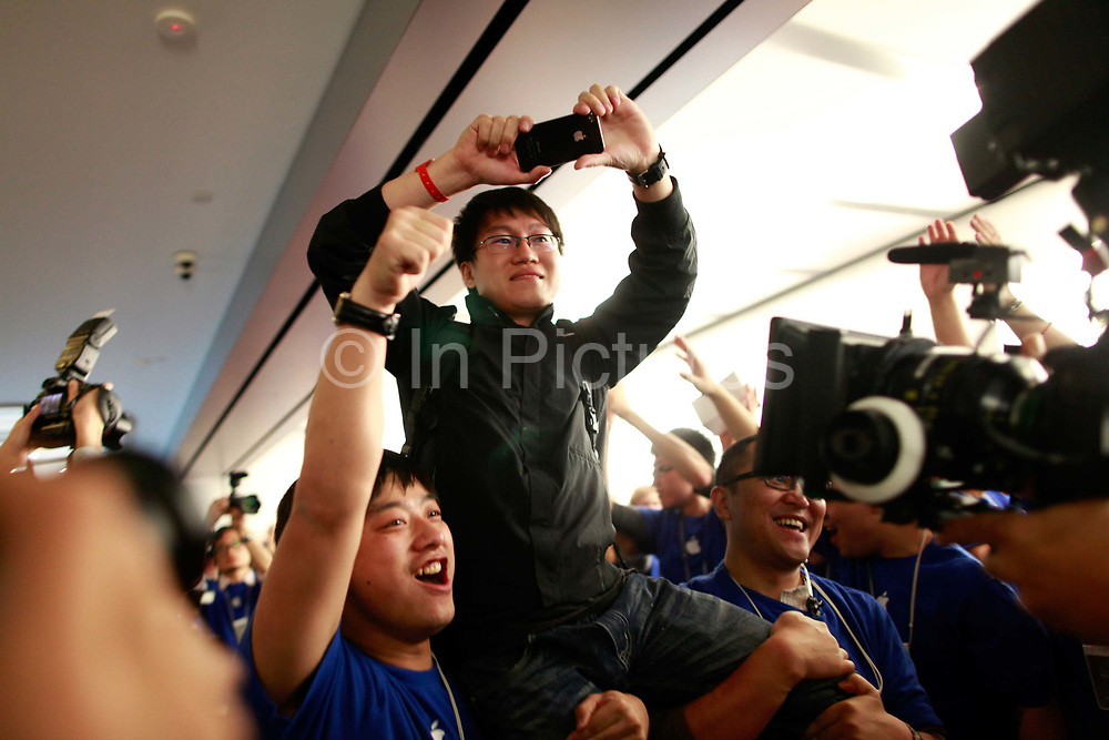 Apple Inc. employees hold up Cui Lizhen, the first customer in line, at the official opening of the company's new store in Shanghai, China, on Friday, Sept. 23, 2011. Apple Inc. is currently has 5 stores in mainland China as it struggles to open enough stores to stave off competiton of its popular iPhones and iPads.
