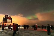Large group of people looking at northern lights (Aurora borealis) at sunrise, Stamsund, Norway