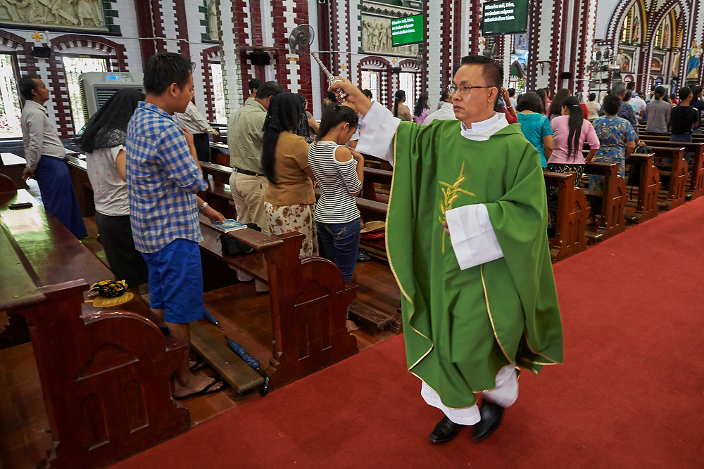 A priest sprinkles Holy Water on faithful at St. Mary's Cathedral in Yangon, Myanmar, Oct. 15. Pope Francis will visit the southeast Asian country Nov. 27-30.  Photo by Paul Jeffrey/kairosphotos.com