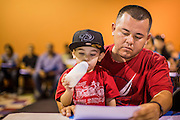 """18 AUGUST 2012 - PHOENIX, AZ: A man holds his son while he goes over paperwork related to """"deferred action"""" during a deferred action workshop in Phoenix. More than 1000 people attended a series of 90 minute workshops in Phoenix Saturday on the """"deferred action"""" announced by President Obama in June. Under the plan, young people brought to the US without papers, would under certain circumstances, not be subject to deportation. The plan mirrors some aspects the DREAM Act (acronym for Development, Relief, and Education for Alien Minors), that immigration advocates have sought for years. The workshops were sponsored by No DREAM Deferred Coalition.  PHOTO BY JACK KURTZ"""