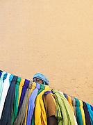 A man selling headscarfs on market day in Djenné, Mali