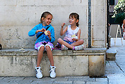 Two children (9 year old and 5 years old) sitting, eating ice-cream. Korcula old town, island of Korcula, Croatia