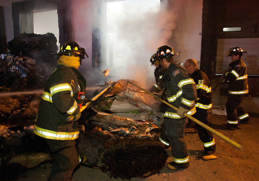 Mansfield, MA 09/13/2011.Firefighters pull burning bales of recycling material out the door of Miller Recycling in Mansfield while fighting a 4 alarm fire there on Tuesday night..Wicked Local Photo by Alex Jones