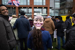 """© Licensed to London News Pictures. 06/12/2020. Manchester, UK. A woman wears a mask on the back of her head with the words """" Marxism is the virus """" . An anti lockdown protest against measures imposed by the British government , designed to limit the spread of Coronavirus , takes place in Piccadilly Gardens in Manchester City Centre . Photo credit: Joel Goodman/LNP"""