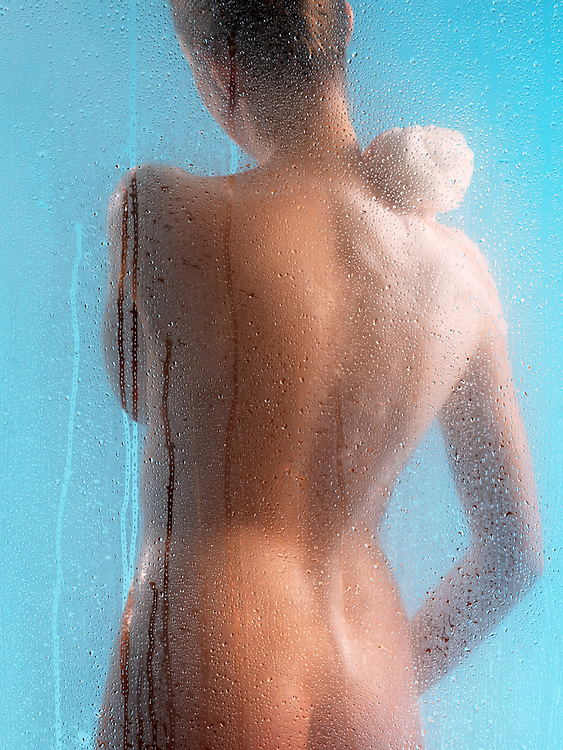 Back view of woman soaping in shower with blue background