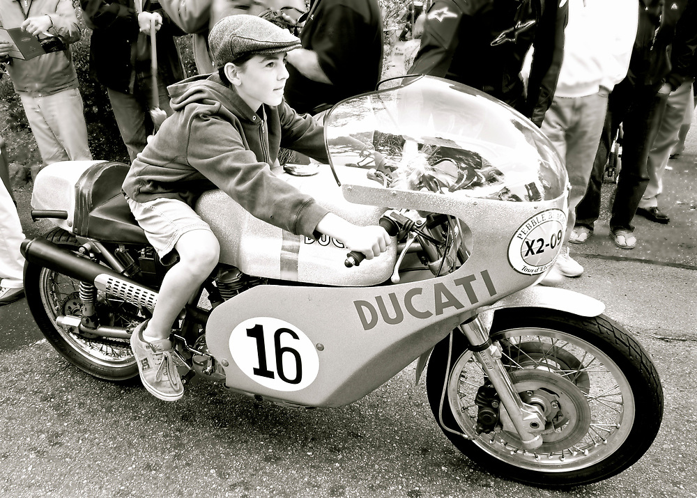 At the pre-event gathering in Carmel for the Pebble Beach Concourse d'Elegance, we caught this young man who had been granted permission to sit on a very rare Italian motorcycle from the early 1970s.  It was this bike, the 750SS that put Ducati on the map when British rider Paul Smart won the Imola 200 in 1972.