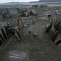 Barrels for whale oil disintegrate near Whaler's Bay on  Deception Island, a volcanic caldera in Antarctica that last erupted in 1969. Anchored in the background is the National Geographic Endeavor.