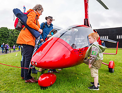 Pictured: Scotland's National Airshow, East Fortune, East Lothian, Scotland, United Kingdom, 27 July 2019 . A packed programme of aircraft old and new planned to take to the skies for the aerial display was marred by poor weather at airfields around the country which meant that many of the promised flights were unable to perform. A child admires a micrilight.<br /> Sally Anderson | EdinburghElitemedia.co.uk