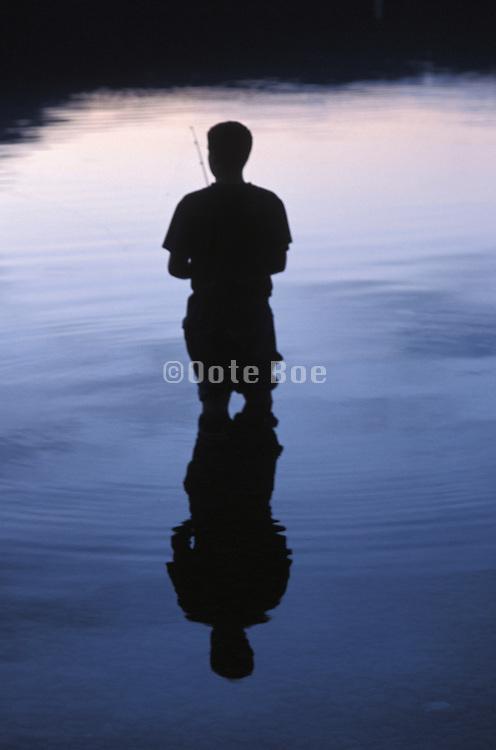 Silhouette of man fishing at Glacier National Park Montana USA