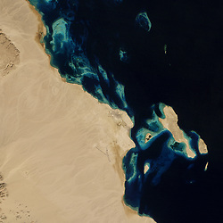 View Image Comparison<br /> View Both Images<br /> In 1985, sand and coral dominated the Red Sea coast in an area about 30 kilometers (19 miles) northwest of Hurghada, Egypt. Aside from a lone road that ran along the coast, the desert landscape was largely untouched by human activity. Three decades later, development has radically reshaped the coastline.<br /> The construction of El Gouna, a resort town, began in 1989. Building proceeded in waves, with a small cluster of summer holiday homes eventually morphing into a year-round community of about 23,000 people. As of 2015, El Gouna included 16 hotels, some 2,700 villas, 3 marinas, an 18-hole golf course, and hundreds of restaurants and shops.<br /> Developers were not content to simply build on the existing landscape. To give<br /> seaside views and easy access to the water to as many El Gouna residents and guests as possible, builders dredged huge amounts of sand from coastal bays and inlets to sculpt the canals, marinas, hotels, and artificial islands of the resort.<br /> The changes to the coast are evident in this pair of natural-color images acquired by sensors on Landsat satellites. The top image was captured by the Thematic Mapper (TM) on Landsat 5 in 1985; the bottom image was captured by the Operational Land Imager (OLI) on Landsat 8 in 2014.<br /> While El Gouna has pledged to become a carbon neutral town, the resort has come with a cost for the local environment, particularly the coral reef ecosystems that make the area so appealing. Construction of coastal hotels and other infrastructure often involved the destruction of fringing reefs along the coastlines, caused by the dredging or dumping of large amounts of sediment.<br /> While it is difficult to distinguish between reefs, underwater sand, sea grass, and algae in natural-color Landsat imagery, some scientists have used other wavelengths to track changes in corals near El Gouna and neighboring Hurghada. The findings indicate the reefs may be in troub