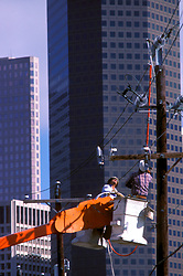 Stock photo of two men in a cherry picker working on power lines in downtown Houston Texas