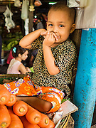 """25 OCTOBER 2015 - INSEIN, MYANMAR:  A child in a produce booth at Danyin Market (also known as Da Nyin) in Insein, Myanmar, about 90 minutes from Yangon. Vendors in the market sell just about everything people in the area need, but mostly it's a """"wet market"""" with fruits, vegetables and meats. Most people in Myanmar still do not have refrigerators in their homes, so people go to market almost every day.    PHOTO BY JACK KURTZ"""
