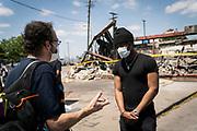 Matt (last name not provided) speaks with Der Speigel reporter Ralf Neukirch along Lake Street in Minneapolis, Minnesota on Monday, June 1, 2020.
