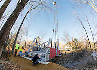 Mark Roberts operates the crane to maneuver the bridge into place over the Tioga River with Ron Mitchell and Chris Clairmont guiding the placement on the Mill Street side in Belmont Village Monday afternoon.  (Karen Bobotas/for the Laconia Daily Sun)