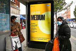 © Licensed to London News Pictures. 16/10/2020. London, UK. A woman wearing a face covering looks at the government's latest COVID-19 advert informing about the tier two restrictions, as London moves to COVID-19 tier two restrictions from tonight, following the government's announcement of tougher measures in the capital to manage increasing cases. From midnight tonight, households in London will not be allowed to mix indoors, including in pubs and restaurants.  Photo credit: Dinendra Haria/LNP