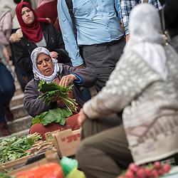 23 February 2020, Jerusalem: A woman sells vegetables on a street in the Jerusalem Old City.