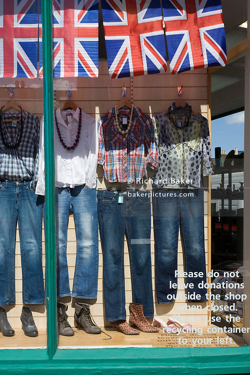 Union Jack flags hanging and clothing on sale in an Oxfam charity shop window display.
