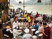 "11 MARCH 2016 - LUANG PRABANG, LAOS:  Tourists at a hotel breakfast buffet in Luang Prabang. The Mekong River is in the background. Luang Prabang was named a UNESCO World Heritage Site in 1995. The move saved the city's colonial architecture but the explosion of mass tourism has taken a toll on the city's soul. According to one recent study, a small plot of land that sold for $8,000 three years ago now goes for $120,000. Many longtime residents are selling their homes and moving to small developments around the city. The old homes are then converted to guesthouses, restaurants and spas. The city is famous for the morning ""tak bat,"" or monks' morning alms rounds. Every morning hundreds of Buddhist monks come out before dawn and walk in a silent procession through the city accepting alms from residents. Now, most of the people presenting alms to the monks are tourists, since so many Lao people have moved outside of the city center. About 50,000 people are thought to live in the Luang Prabang area, the city received more than 530,000 tourists in 2014.      PHOTO BY JACK KURTZ"