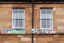 Glasgow, Scotland, UK. 13 May 2021.At approx 5.30 pm police released two men from a Home Office detention vehicle. Accompanied by lawyer Aamer Anwar the men walked to a nearby mosque surrounded by hundreds of police and supporters who had previously been surrounding the vehicle and sitting on the street. Pic; protest signs hung outside tenement flat windows.   Iain Masterton/Alamy Live News
