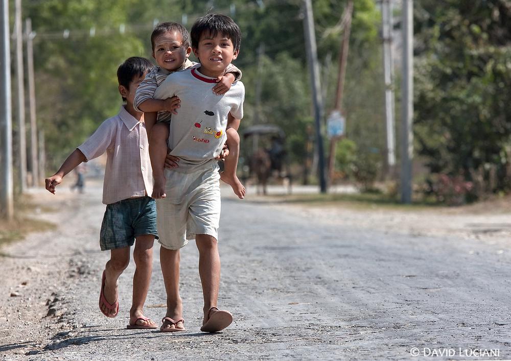 Three boys enjoying their walk on a main street in Nyaung Shwe.