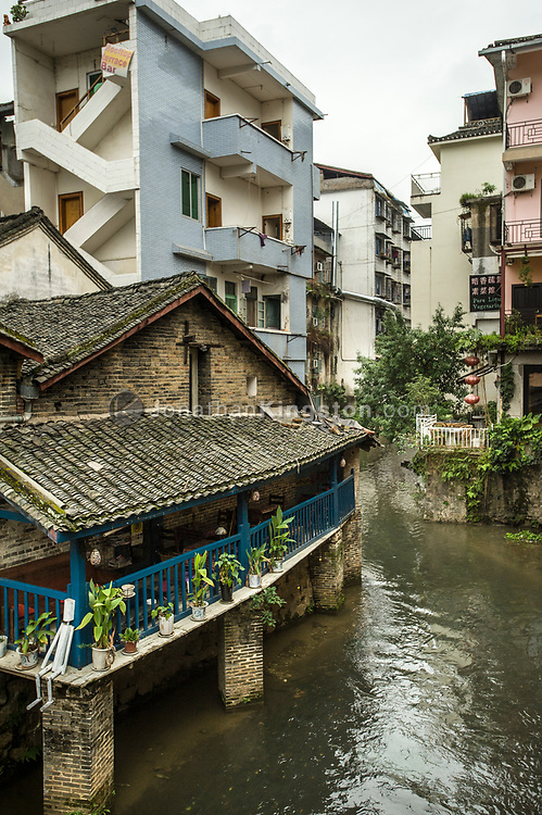 A restaurant and apartment buildings rise above a small river in Yangshuo, China.