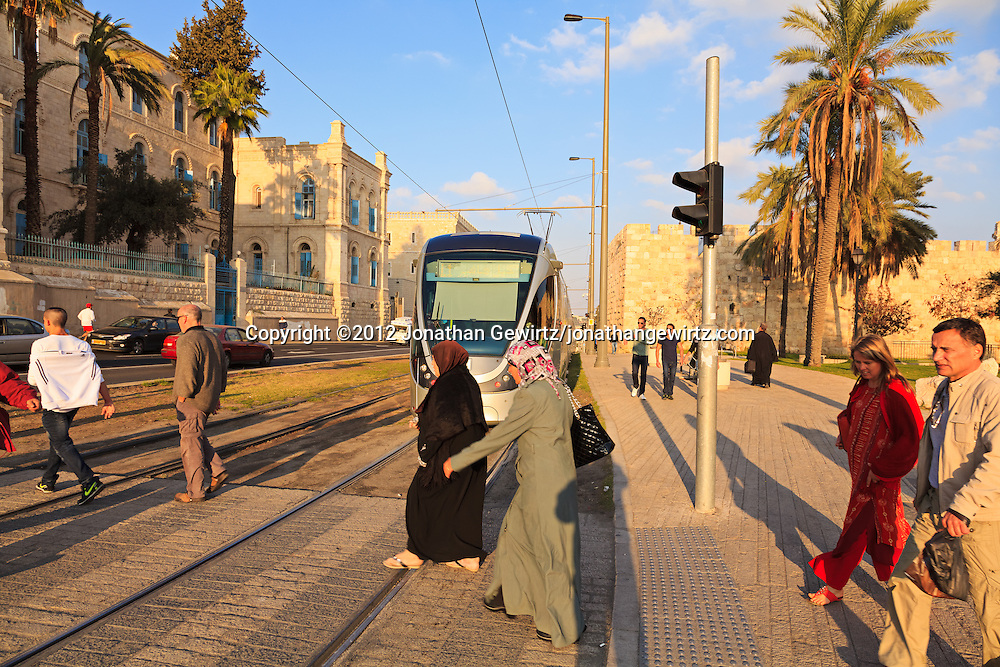 Pedestrians cross light-rail tracks in front of a train on Sultan Suleiman Street at the junction of Jerusalem's old and new cities. WATERMARKS WILL NOT APPEAR ON PRINTS OR LICENSED IMAGES.
