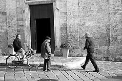 Die persona attendono il ritorno del parroco davanti all'entrata della chiesa nel centro storico di Racale (LE)