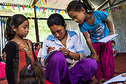 Children check their work with the teacher as they learn basic english in the SOS Children's Villages Child Care Space in Rayale, Nepal on 1 July 2015. The Child Care Space was set up by SOS Children's Villages soon after the earthquake so that they children of the village can come together to play, learn, and get over the trauma of the disaster, while their parents can be free to reconstruct their homes and go off to get rations and relief kits. Photo by Suzanne Lee for SOS Children's Villages