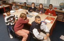 Multiracial group of junior school children sitting around desks in classroom,