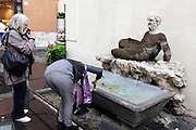 two female tourist trying to photograph an old sculpture in Rome Italy.
