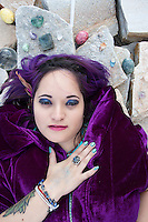 Heart and soul magical woman in a purple cloak with a crystal crown chakra head altar for sky gazing meditation in sacred stone place.