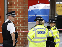 © Licensed to London News Pictures. 06/07/2021. London, UK. Police guard a crime scene on Woolwich New Road in south east London after a 15 year old boy was stabbed to death. Officers were called at 17:23hrs on Monday, 5 July to reports of a stabbing on Woolwich New Road, SE18. Police found a 15-year-old boy suffering from a stab injury. They immediately provided first aid prior to the arrival of the London Ambulance Service. Despite their efforts, he was pronounced dead at the scene. Photo credit: Peter Macdiarmid/LNP