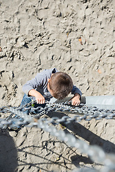 Small boy playground climbing chain from above