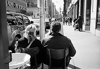 Couple watching the world go by on the sidewalk in front of Starbuck on Lexington Avenue and 87th street, New York City.