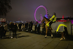 © Licensed to London News Pictures. 31/12/2020. London, UK. Mounted police move crowds gathered just before midnight on the Embankment in sight of The London Eye ferris wheel ahead of midnight and a muted New Year's Eve in central London. Photo credit: Peter Macdiarmid/LNP