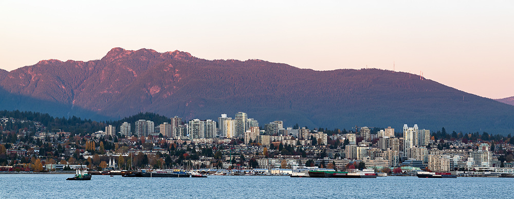 Burrard Inlet and the buildings of North Vancouver while sunset projects a warm glow on Mount Seymour. Photographed from Brockton Point at Stanley Park in Vancouver, British Columbia, Canada.