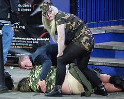 © Licensed to London News Pictures . 27/12/2016 . Wigan , UK . A woman in fatigues lies collapsed on the pavement as others tend to her . Revellers in Wigan enjoy Boxing Day drinks and clubbing in Wigan Wallgate . In recent years a tradition has been established in which people go out wearing fancy-dress costumes on Boxing Day night . Photo credit : Joel Goodman/LNP