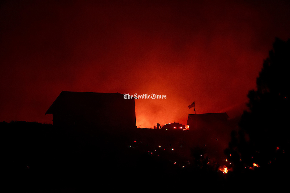 Firefighters work at a house near the town of Twisp, Wash. early in the morning Thursday, Aug. 20, 2015.<br /> <br /> Erika Schultz / The Seattle Times
