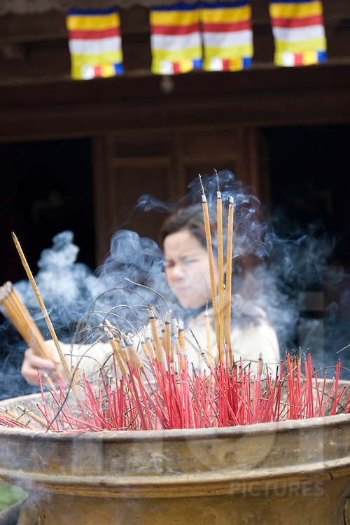 Sticks of encense are burning in a pagoda's cencer. A vietnamese woman in the background brings new sticks and closes her eyes to avoid smoke. Vietnam, Asia