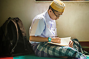 21 FEBRUARY 2013 - BANGKOK, THAILAND: A boy reads the Koran in Haroon Mosque in Bangkok. Haroon Mosque, originally known as Masjid Ton Samrong, is one of the first mosques in Bangkok and was originally built in the middle of the 19th century. It was established by Musa Bafadel, an Indonesian trader from Pantiyanah, south of Borneo in what is now Indonesia. The mosque is now named after Haroon, Musa Bafadel's son who inherited his father's trade empire. The mosque was originally built of wood, but the wood decayed in Bangkok's climate and is now built of bricks and mortar. The wood was salvaged and used in the construction of the mosque.      PHOTO BY JACK KURTZ
