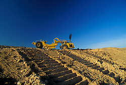 Stock photo of a large tractor parked at the top of a large dirt incline