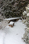 Snow covers a stone bench at the Asticou Azalea Garden, Northeast Harbor, Maine.