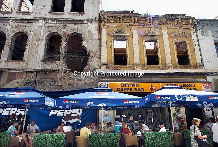 Kroatië, Vukovar, 6-7-2008Café in het karkas van gebouwen, uitgebrand en door kogelinslagen beschadigd tijdens de oorlog die hier van augustus tot november1991 woedde. De stad werd volledig in puin geschoten en uiteindelijk wisten de Serven haar in te nemen ten koste van duizenden burgerslachtoffers en grote wreedheden. Nog steeds zijn er gebouwen niet gesloopt of hersteld. Toch is al veel gedaan aan de wederopbouw. In de zomer van 1991 woedde er oorlog in delen van Kroatië, wat zich in de lente onafhankelijk had verklaard en uit de Joegeolslavische federatie was gestapt. Vukovar lag aan de grens met Servië, en in het gebied woonde een groot percentage Serven die aansluiting zochten bij Servië en een burgeroorlog starten.Vanaf de maanden juli en augustus 1991 heeft de Kroatische regering geleidelijk  de controle verloren van Oost-Slavonië. Paramilitaire troepen en de plaatselijke Servische milities, vaak ondersteund door eenheden van het JNA, het nationale joegoslavische leger, verdreven overheidsfunctionarissen en wierpen barricades en mijnenvelden op.Het JNA nam posities aan de andere kant van de Donau, en JNA gunboats bewaakten de rivier. Mortier beschietingen begonnen in juli, en de lange afstand artillerie aanvallen vanaf begin augustus. Tegen het einde van augustus was de bevolking van de stad gedaald tot ongeveer 15.000 mensen.  Zij bestond uit een mengsel van Kroaten, Serviërs en andere nationaliteiten.  Vukovar was grotendeels omringd door Serviërs gecontroleerde gebied, en vanaf eind augustus onderworpen aan intense beschietingen en lucht aanvallen. Uiteindelijk werd de stad in puin geschoten en bezet door Serviërs. Pas sinds 1998 is het gebied weer terug bij Kroatië. Er zijn ong. 6000 doden bij het beleg gevallen, waaronder ruim 3000 burgers.Foto: Flip Franssen/Hollandse Hoogte