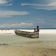 Papuan kids playing with a logboat on a white sandy beach.