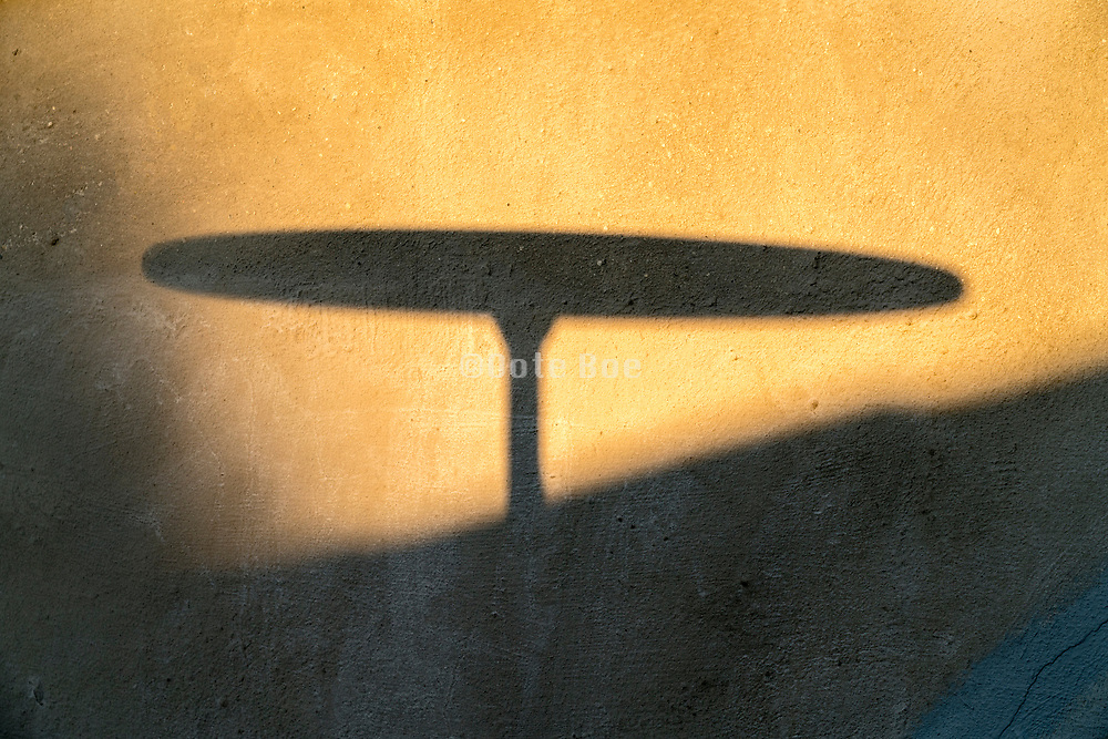round bistro table silhouette shadow projection on a wall
